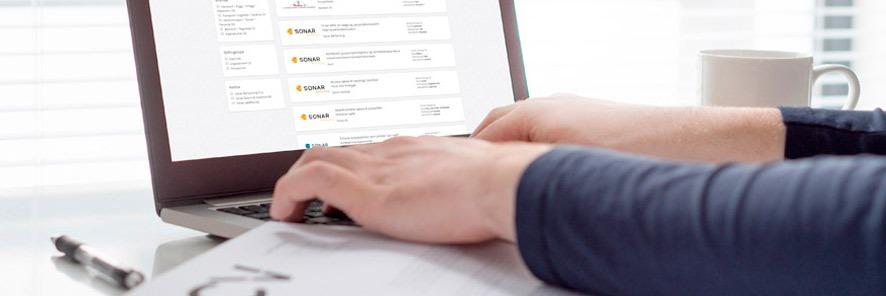 Bilde som viser deler av en åpen laptop. To hender hviler på tastaturet. Nettsiden som er åpen viser ledige stillinger hos Sonar. Ved sidene av laptopen befinner det seg papir og penn på venstre side og en kaffekopp på høyre side.