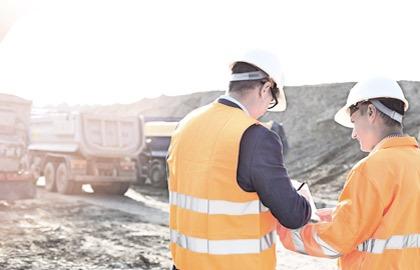 Bilde fra en utendørs arbeidsplass. To arbeidere med hvit hjelm og oransje vester står med ryggen til. I bakgrunnen skimtes tre lastebiler for transport av grus.