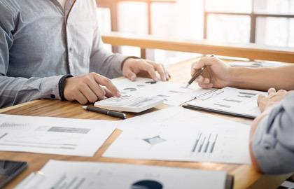Bilde tatt fra siden av et skrivebord På den ene siden av bordet kan man skimte overkroppen til en person som er vendt mot et papir på bordet og som samtidig trykker på en kalkulator. På den andre siden av bordet kan man skimte armene til en person som peker med en penn på papiret. Skrivebordet er fult ark.