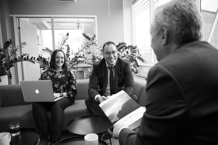 Bilde i svart-hvitt som viser en mann og en kvinne som sitter i en sofa. Kvinnen har en laptop å fanget. Begge kikker smilende bort på en mann som sitter med ryggen til. Han holder en brosjyre å hånden. I bakgrunnen skimtes planter, vinduer og en kontordør.