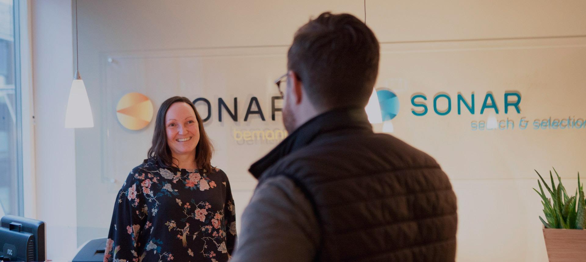 Bilde av en smilende kvinne i blomstrete genser. Hun kikker mot en mann som har ryggen til kameraet. I bakgrunnen skimtes logoen til Sonar Bemanning på veggen.