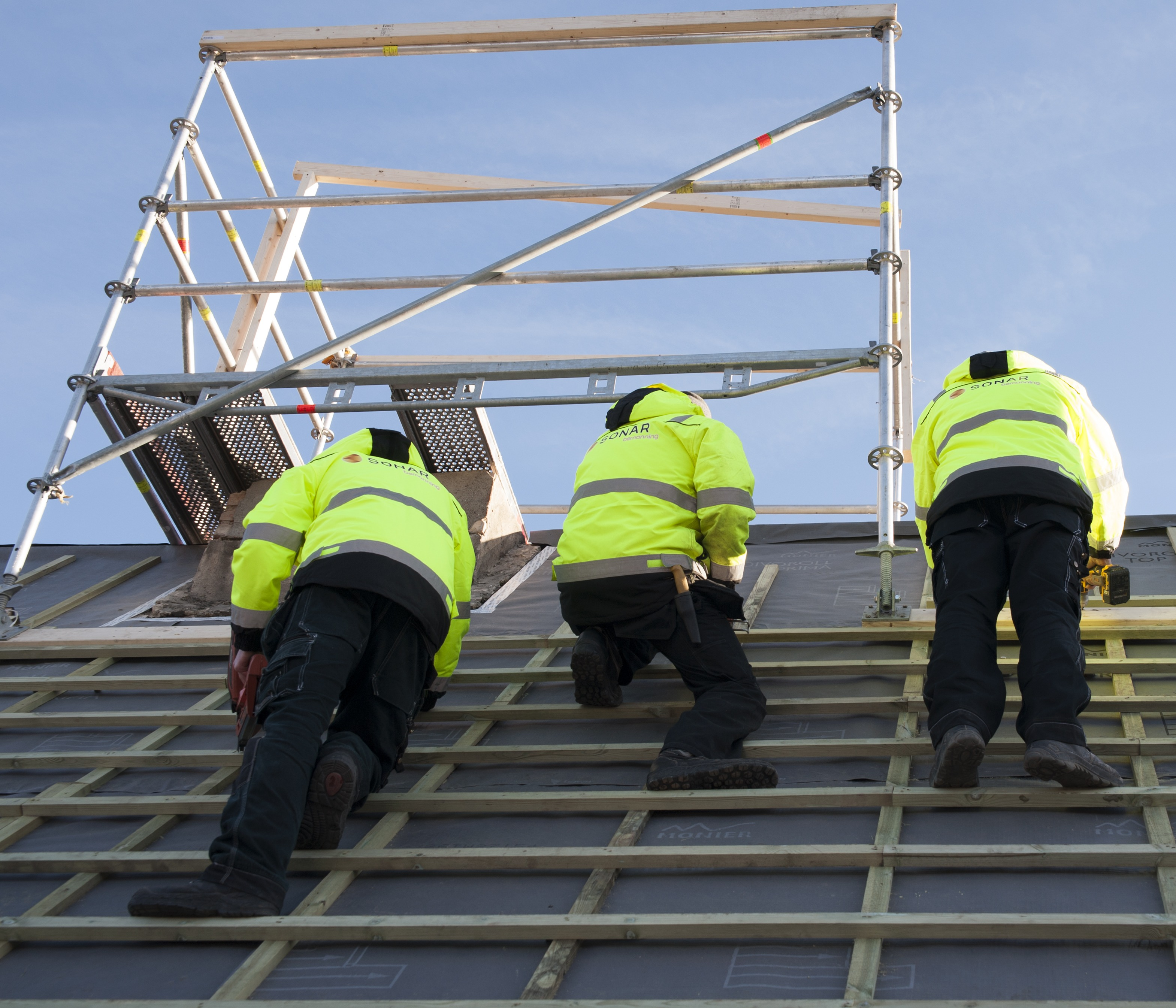 Bilde i froskeperspektiv som viser tre bygningsarbeidere iført gule jakker fra Sonar Bemanning. De befinner seg på toppen av et tak. Over dem er det et stilas.
