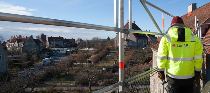 """Bilde i bannerformat som viser et nabolag fra høyden. Det er tatt fra et stilas og det er mulig å se metallstenger vertikalt og horisontalt. Til høyre på bildet står en person i gul arbeidsjakke med påskriften """"Sonar""""."""