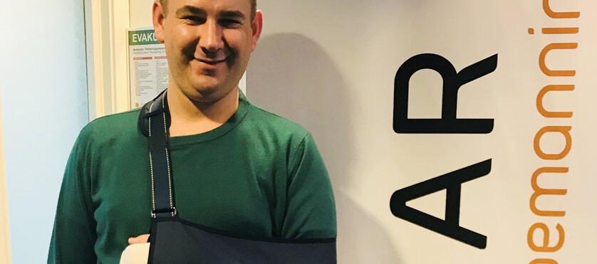 Bilde av den polske tømreren Andrzej Bankowski. Han kikker smilende inn i kameraet med den ene armen i slynge.