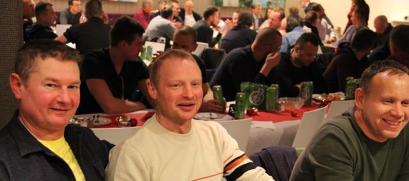 Bilde av tre glade, mannlige medarbeidere hos Sonar som koser seg på julebord. I bakgrunnen skimtes flere bord med medarbeidere.