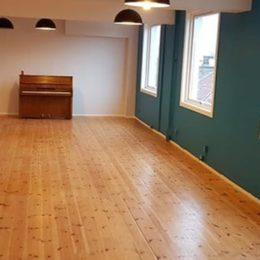 Bilde av et oppholdsrom på Fattighuset i Grønlandsleiret som ble nyoppusset av håndverkere fra Sonar. Det er et bart rom med tregulv, et piano i enden og fem taklamper.